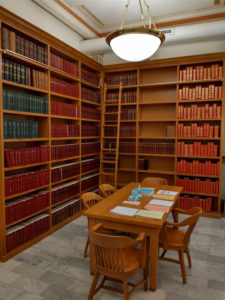 Picture of the new library space, featuring a work table and wooden shelving, a ladder, and research books.